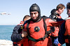 """Squad 1 SCBA (self contained breathing apparatus) rescuer Raol Ochoa, """"Och"""" to his teammates, being helped out of the water at Montrose Harbor breakwater after sucessfull rescue attempts of a man and his dog."""