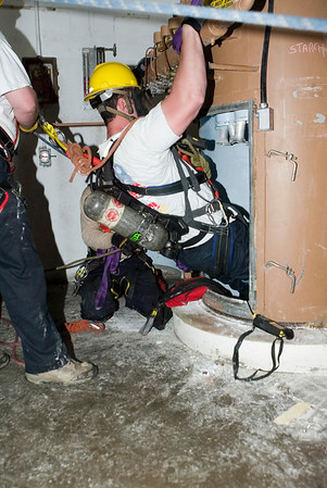 "Dave Leon<br /> of CFD Squad 1 preparing to descend in a silo the bottom of which contains a mannequin ""victim"" during confined space rescue drill in course offered by the U. of Illinois Fire Service Institute."