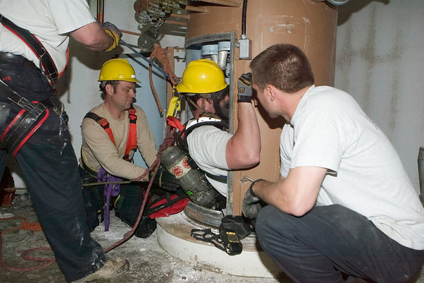 """Dave Leon<br /> of CFD Squad 1 preparing to descend in a silo the bottom of which contains a mannequin """"victim"""" during confined space rescue drill in course offered by the U. of Illinois Fire Service Institute."""