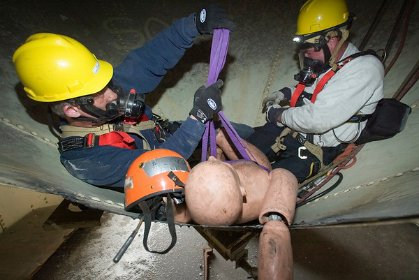 """Preparing the """"Victim"""" for Rescue<br /> Special Operations Squad 7 Engineer Ron Zymali (l) and Capt. John Collins of CFD Squad 1 adjusting special victim harness, knon as a """"halfback harness"""", used in a confined space rescue drill conducted by the U. of Illinois Fire Service Institute April 10-14, '06."""
