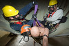 "Preparing the ""Victim"" for Rescue<br /> Special Operations Squad 7 Engineer Ron Zymali (l) and Capt. John Collins of CFD Squad 1 adjusting special victim harness, knon as a ""halfback harness"", used in a confined space rescue drill conducted by the U. of Illinois Fire Service Institute April 10-14, '06."