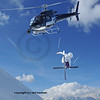 helicopter equiped with a steady cam filming a ski jumper crossing his skis for a high jump