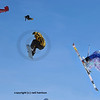 2 snowboarder and a skier jump out of a low flying red bi-plane