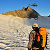 a helicopter delivers goods to a high mountain refuge (right), while a climber on  a glacier looks on.