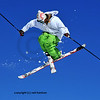 skier in green and white clothes performing a tele-heli with skis crossed at the same time as executing a full spin (in this shot, facing backwards)