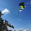 a snowboard jumper jumping over a tree stump into a sky with fair weather clouds. snow covered mountains in the background