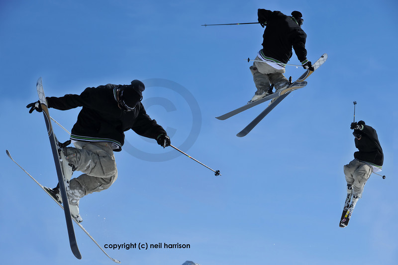 a skier performing a jump during which he makes a full turn and touches one of his skis