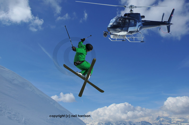 helicopter equiped with a steady cam filming a ski jumper in green clothes crossing his skis for a high jump