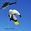 filming with a steady cam mounted on the front of a helicopter of a snowboarder jumping