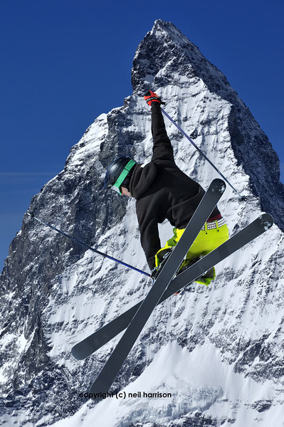 the peak of the Matterhorn in switzerland with a ski jumper in the foreground