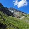 A glacier descending from the Mischabel massif emerges into a steep grassy valley in southern switzerland.