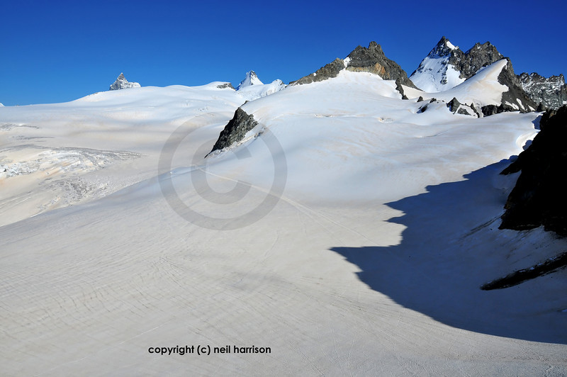 Panoramic view of the Mont Mines glacier with from the left the Matterhorn; Dent d'Herens and on the right the collection of peaks which make up the Dents de Bertol. The track across the glacier is the main route taken by the Patrouille des Glaciers and the Haute Route