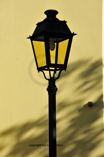 Yellow glass street lamp in front of mustard coloured wall with shadows, created by low sunlight.