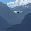 An Antonov A-2 bi-plane flying into the alps. In the far distance a small single winged passenger plane can also be made out.
