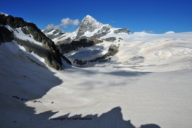Dent Blanche  (4357m) with the Grand cornier to it's left. In the foreground the mont mines glacier. On the surface of the ice, the yellow-orange colour is caused by sand blown from the sahara desert.