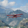 a red biplane flies low over a medievel castle in southern switzerland. this model is an Antonov AN-2. The castle is the chateau of Tourbillon. In the background the Bernese Alps