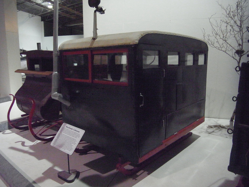 An enclosed horse-drawn sleigh, with built in wood stove!