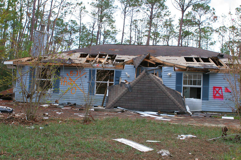 "As you traveled farther inland from the coast into Hancock County some of the homes were intact.  Most of these homes were searched post storm for survivors.  In this picture you can see a blaze ""X"" on the left side of the house with writing.  This is a standard search and rescue procedure.  The left side of the ""X"" indicates the state and what number team searched the house.  The top of the ""X"" indicates the date the house was searched.  If there were survivors or bodies that would be indicated on the right side and lower portion of the ""X"".  As you can see this house was searched by Virginia Team 2. There are still 273 people missing."
