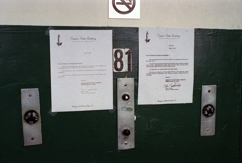 Elevator, 81st floor. Full resolution reveals the text of the posted letters.