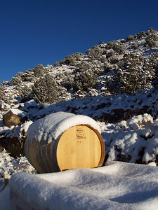 A snow covered barrel and mesa behind the winery.