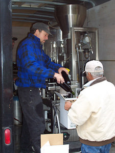 """Bottling is done by a mobile bottling machine (called a """"bottling line"""") shared by four NM wineries. Rather than sitting unused for long periods of time, this bottling line is kept on a trailer and pretty much in constant use somewhere in New Mexico. Here Chris and Armando box up some bottled wine."""