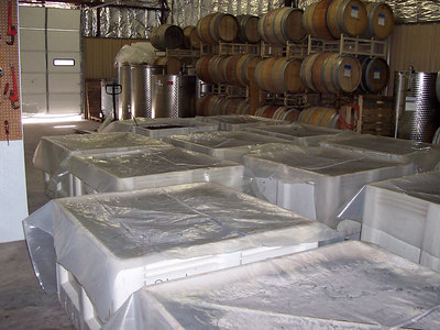 Red grapes fermenting in the winery. Red grapes will ferment this way for a week to ten days... until all the sugar in the juice has been consumed by fermentation. The plastic sheets help hold in carbon dioxide gas from fermentation which makes the wine fresher and prevents oxidation.