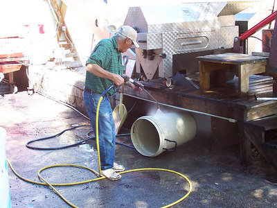 Armando cleans equipment with the pressure washer.