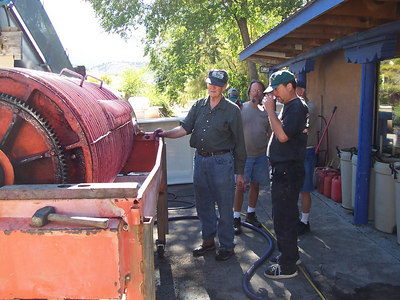 Dick, Jerry and Chris wait on the press to finish a batch of red wine. The thick hose on the ground is pumping the wine to a tank inside the winery