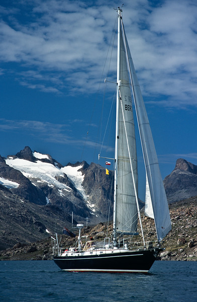 Scan of original slide. Morgan's Cloud sails in a gentle breeze in front of one of the many awe inspiring mountains lining the shores of Prins Christians Sund in southern Greenland.  Cruising in places like this focuses us on making sure that the rig is detailed in every way we can think of.