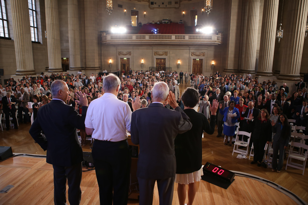 Former Director of AmeriCorps, John Gomperts, Director of AmeriCorps, Bill Basl and Harris Wofford reciting the AmeriCorps pledge with audience. Corporation for National and Community Service Photo.
