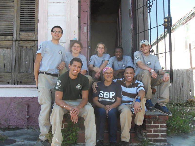 River 6 taking a team photo with a home owner and SBP staff member