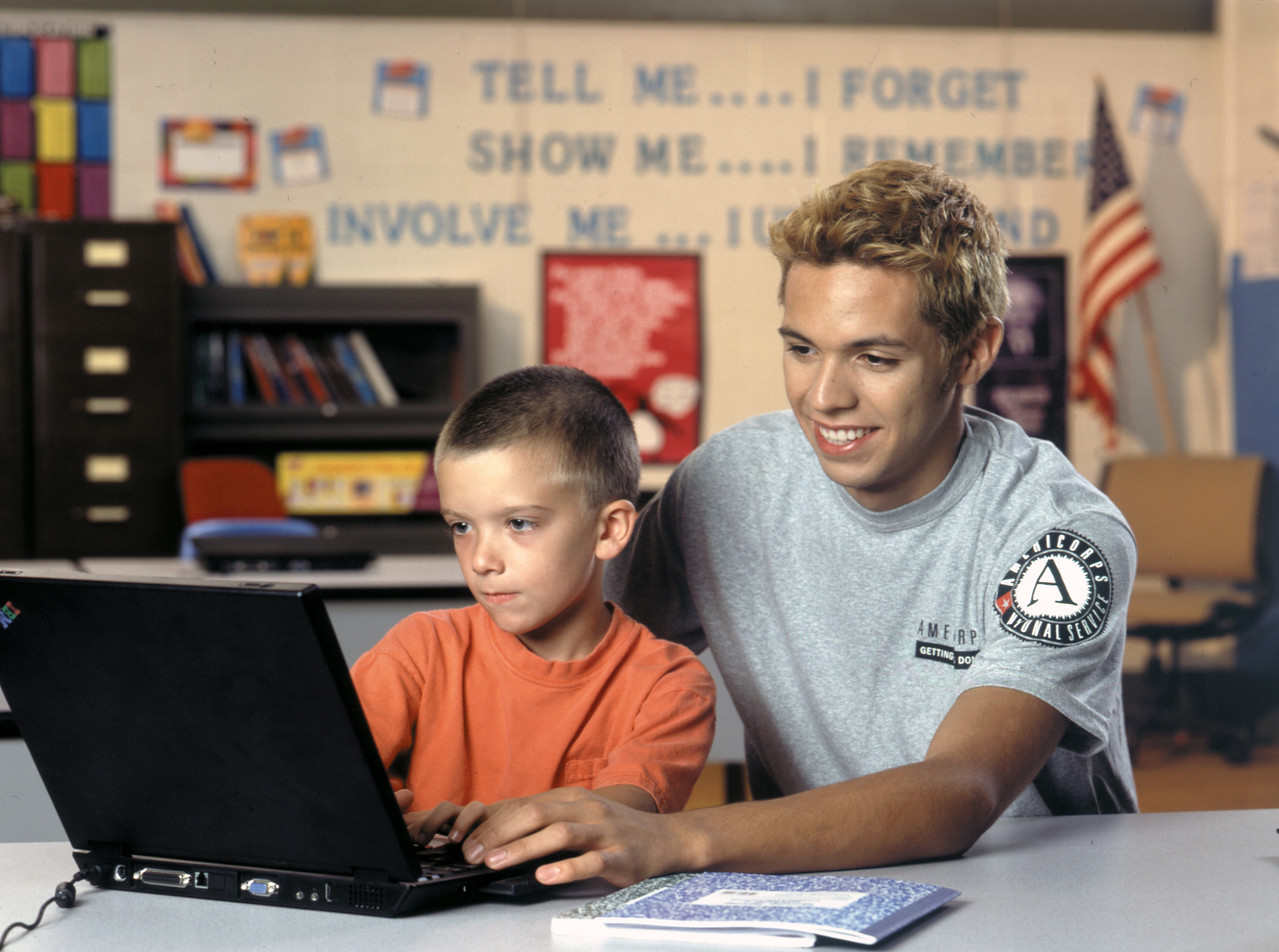 An AmeriCorps member works with a child in a classroom during a tutoring session. Corporation for National and Community Service Photo.