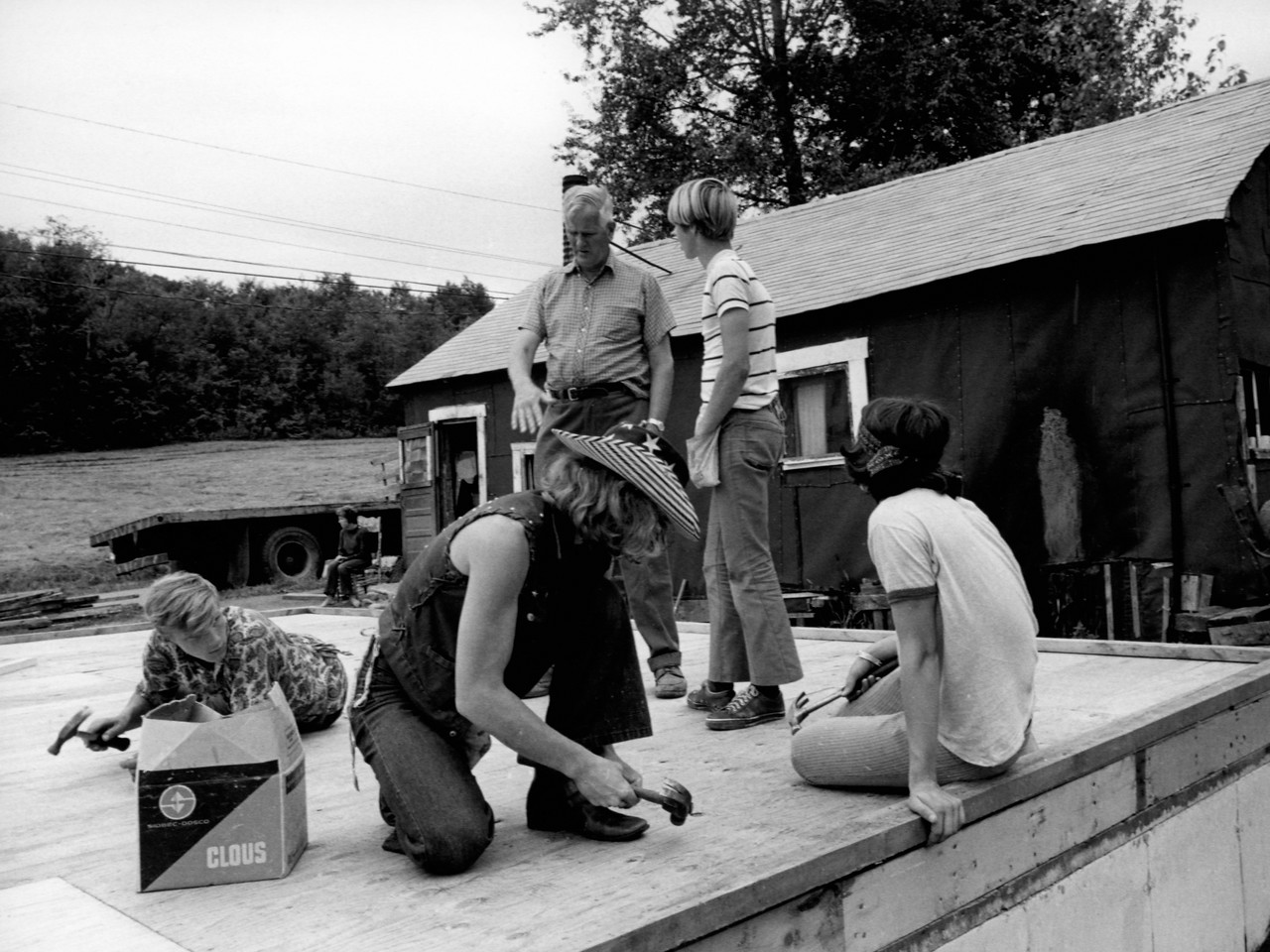 """""""Working with kids keeps me young,"""" claims VISTA member Charles Jackson, 60, who worked on a home repair and construction project near Island Pond, Vermont, in 1983. Jackson and this group of New York City trainees are building a house to replace the shack in the background. Jackson, a native of Vermont and a former field executive for the Boy Scouts, has been a VISTA volunteer for three years. (© 1983 Corporation for National and Community Service - Office of Public Affairs)"""