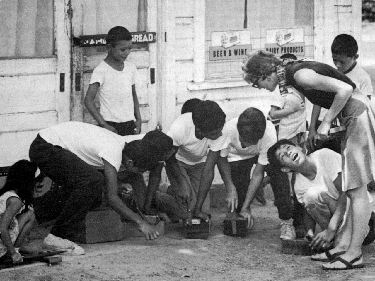 Lucy Norman gathers with a group of Mexican-American youngsters in front of a converted grocery store that has been her home since she began her VISTA assignment in February 1965 in a colony of migrant workers in California. Lucy is helping the boys realize their ambition for a community center. She also organizes English classes for preschoolers and helps their parents obtain public services available to them. (© 1965 Corporation for National and Community Service- Office of Public Affairs)