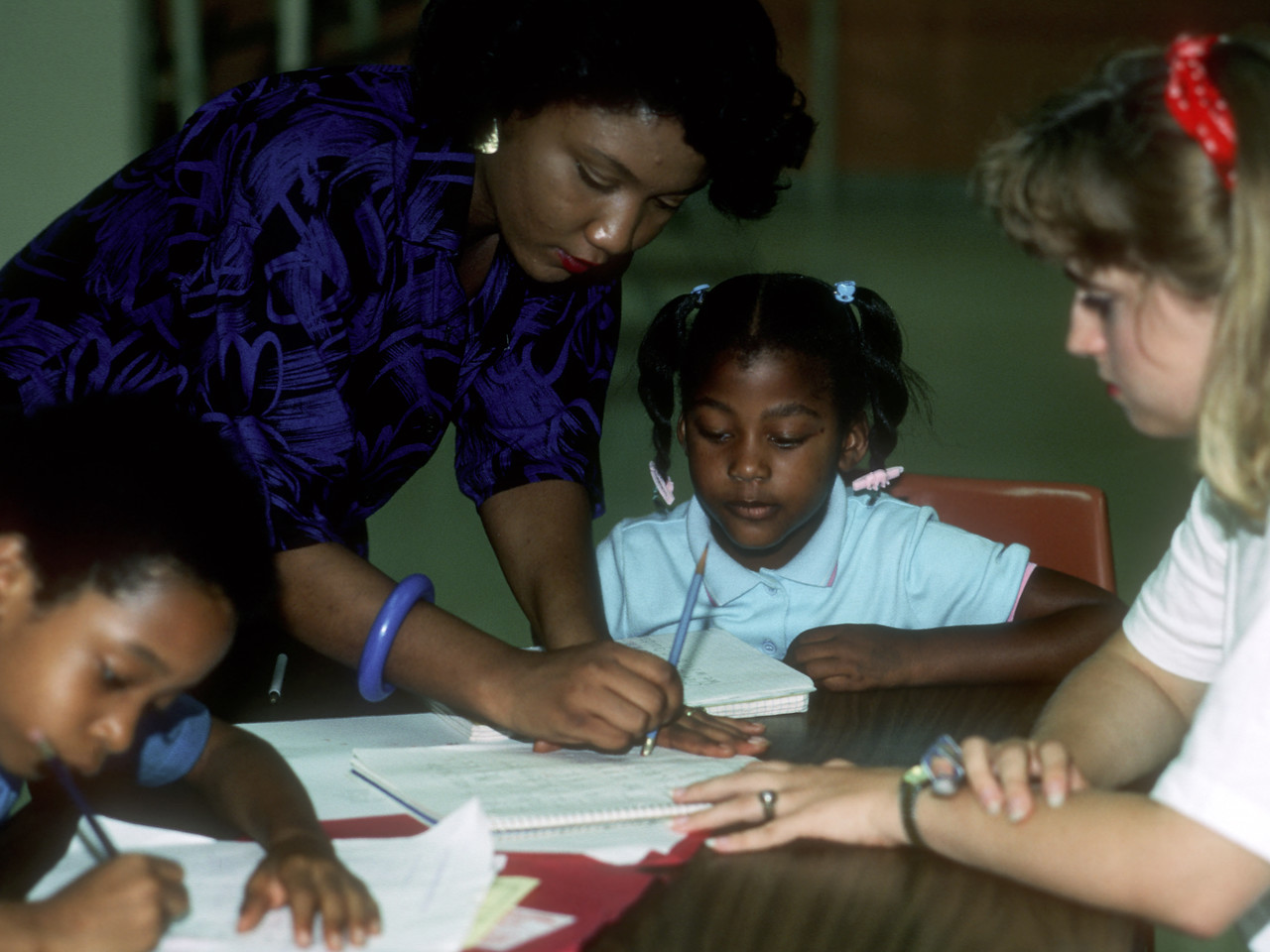VISTA member Jonelle Jones (left) and community volunteer Lida O'Neill tutor neighborhood youngsters in 1986 at the South Baton Rouge Community Development Association in Louisiana. (© 1986 Corporation for National and Community Service - Office of Public Affairs)