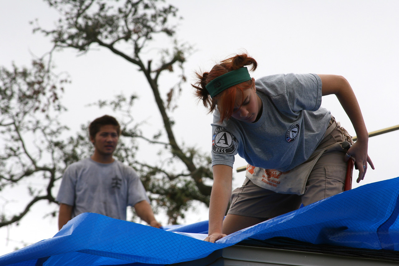 An AmeriCorps member serving with the Washington Conservation Corps, left, joins an AmeriCorps NCCC member in covering the roof of a Florida home with plastic sheeting to protect the house from the elements until permanent repairs can be done. Teams of AmeriCorps members from several states traveled to Florida following the summer''s hurricanes to help with recovery efforts. Corporation for National and Community Service Photo.