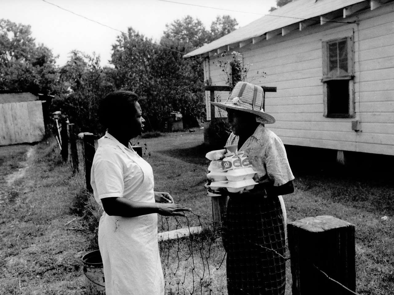 """When VISTA Alice Fay White, 23, of Opelousas, Louisiana, originally arrived in Little Rock in 1972, there was no assignment for her, so she began to seek funds and support for a senior citizen hot lunch program in Sweet Home, Arkansas. She got her funding through a Community Action Program emergency food and medical program grant, and she became the """"coordinator"""" to keep the program going, working in the kitchen preparing food and delivering the lunches. In this photo, a staff member delivers lunch to an elderly woman in Sweet Home. (© 1972 Corporation for National and Community Service - Office of Public Affairs)"""