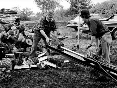 A veteran woodsman, Bill Butler (left), helps a co-op member split wood on a two-man operator mechanical wood splitter. Butler is a VISTA member assigned in September 1979 to the Maine Citizens Committee for Utility Rate Reform, a group organizing elderly and low-income area residents to convert to wood fuel. Butler also helps to put together municipal firewood projects in Portland and Bangor to make good firewood available and affordable to low-income urban dwellers. (© 1979 Corporation for National and Community Service - Office of Public Affairs)