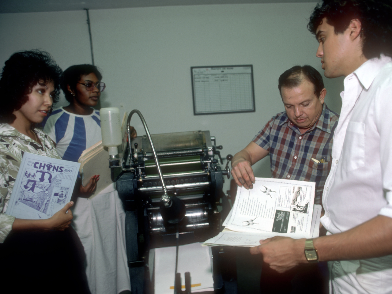 Printer Isidro Garcia (plaid shirt) discusses the publication of the next issue of CHINS Notes, a magazine reflecting the experiences of young people in Las Cruces, New Mexico, with VISTA members (left to right) Annette Alvarez, Norma Scott, and Derek Rubio in 1986. (© 1986 Corporation for National and Community Service - Office of Public Affairs)