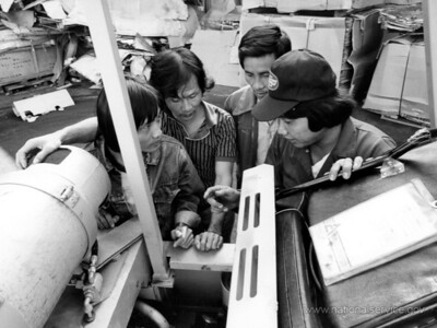 VISTA member Do Hiew (right) teaches Vietnamese refugees forklift maintenance in San Francisco. He began his VISTA assignment with Project Achieve in May 1980 as a recruiter and outreach worker. Hiew, 30, came to the United States in October 1979. He has a degree in economics. (© 1980 Corporation for National and Community Service - Office of Public Affairs)