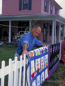 James Thibeault moved from Massachusetts in 1970s to serve as a VISTA in Malden, West Virginia. While there, he joined coal miners' wives and widows to start Cabin Creek Quilts Cooperative, which is still operative today. In this 1999 photo, Thibeault, who was then director of the cooperative, hangs a quilt on the fence for passing visitors to see. Today, Thibeault is a gardener for Good Living Assisted Living, which he owns, and an active volunteer with Jisaidie Cottage Industries, a handicraft cooperative in Nairobi, Kenya. Thibeault's volunteer assistance helped Kenyan artisans living with HIV/AIDS penetrate European and American handicraft markets. (© 1999 Corporation for National and Community Service- Office of Public Affairs)