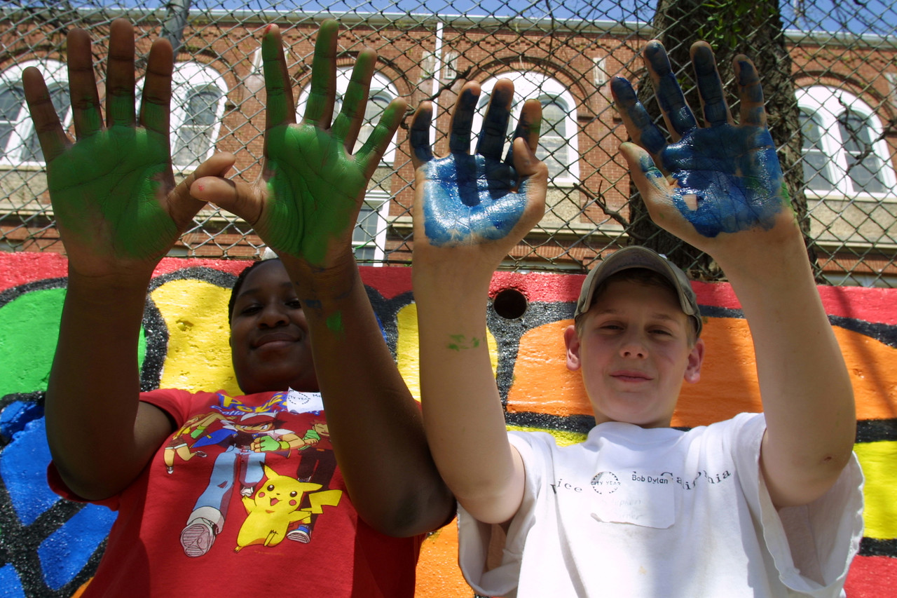 Students display their colorful hands after working on a mural as part of a Learn and Serve America project. Learn and Service America is a program of the Corporation for National and Community Service and enables students to make meaningful contributions to their community while building their academic and civic skills. Corporation for National and Community Service Photo.