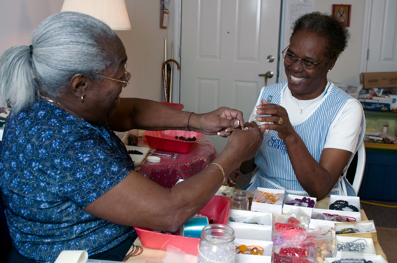 A Senior Corps volunteer with the Senior Companion Program works with one of her clients to create beaded jewelry.