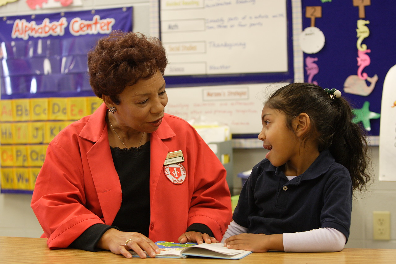 A Foster Grandparent reads with a young student in her classroom.