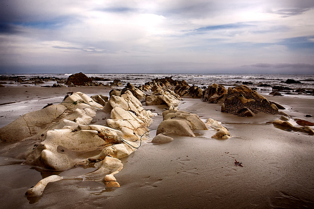 "Headed to the beach for a few days..... didn't have time to stick around until the ""golden hour"" so had to go with what I had.. Thankfully there was some cloud cover to soften the light a bit... I liked the smooth texture of these rocks after years and years of salty surf pounding them... <br /> Day 87 of 2013<br /> 03-28-2013"