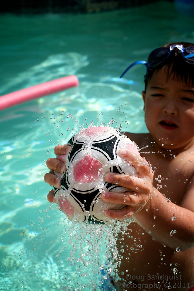 Trying to capture summer is fun, so many ways to capture the fun times! This is a stitched soccer(or football for those anywhere other than the USA) that has become a pool toy!... When it's submerged and all the air is allowed to escape it fills with water and then when squeezed it sends water in all directions, kind of like a sprinkler.. Reece's hands are almost strong enough to get the sprinkler effect going.. He'll keep practicing and probably get it by the end of summer! <br /> 07-23-2011