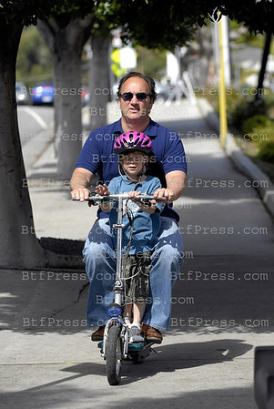 James Belushi take a ride with his kid on his electric bike in Brentwood, California.