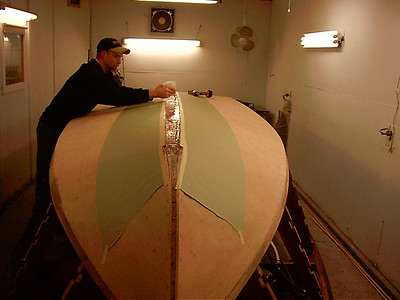 Applying West System epoxy to glue keel cap in place.