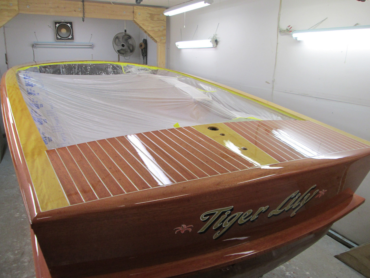 Starboard rear view of deck seams installed with the first coat of varnish over the seams.
