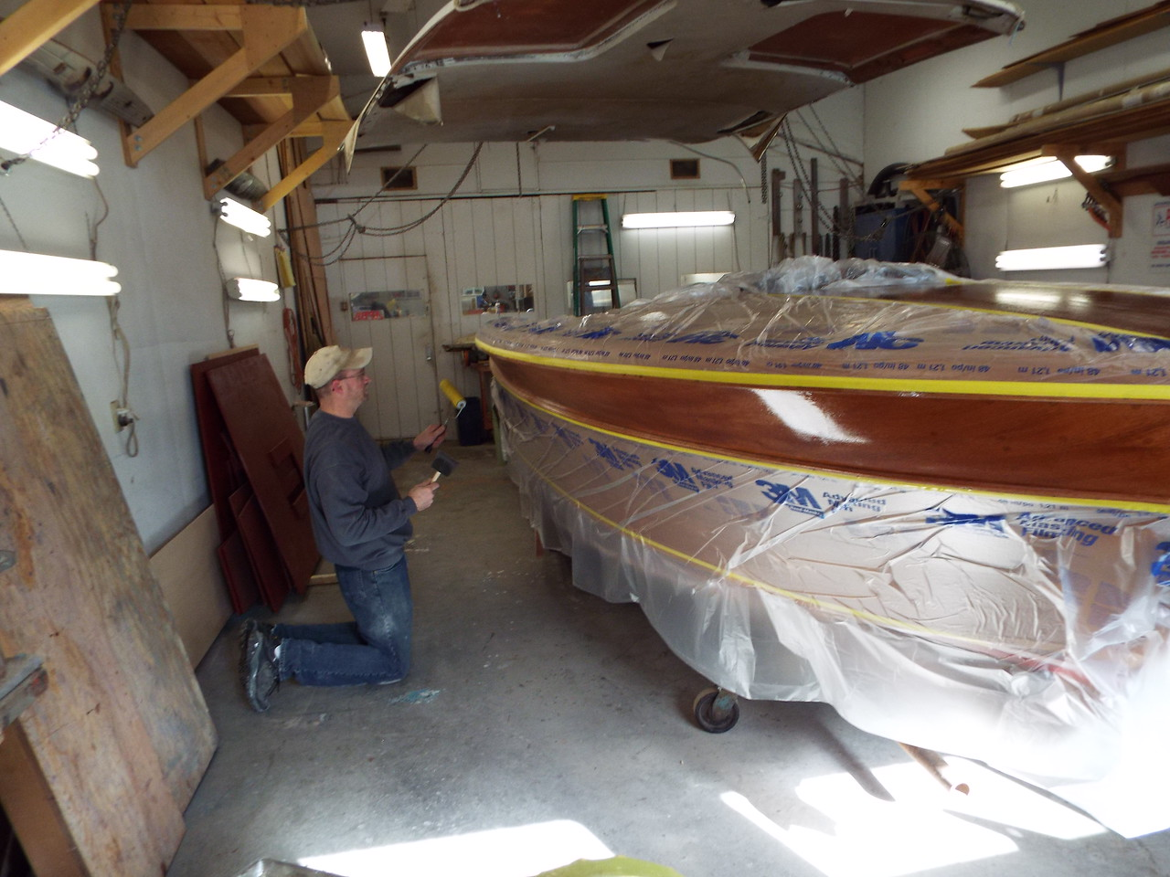 Final coat of epoxy being applied to the starboard top plank.